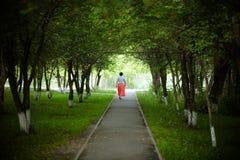 Eine Frau geht durch die Gasse lizenzfreie stockfotos