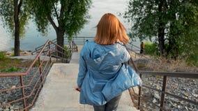 Eine Frau geht hinunter die Treppe zur Flussbank stock footage