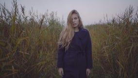 Eine Frau geht Recht unter hohem Gras entlang einem Pier in einem Mantel stock video footage