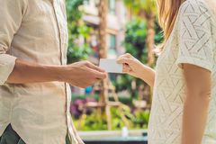 Eine Frau gibt zu einer Mannsicherheitsschlüsselkarte oder -Visitenkarte stockbild