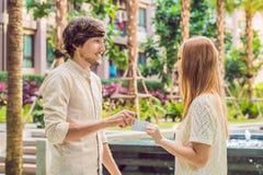 Eine Frau gibt zu einer Mannsicherheitsschlüsselkarte oder -Visitenkarte lizenzfreie stockfotos