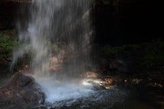 Eine Frau ging mit einem Regenschirm gehend in die Höhle hinter den Wasserfall Lizenzfreie Stockfotografie