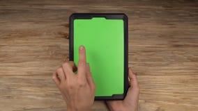 Eine Frau hält einen Tablet-PC mit einem grünen Schirm für Ihren eigenen kundenspezifischen Inhalt stock video footage