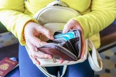 Eine Frau hält eine Geldbörse und zählt russisches Geld lizenzfreie stockbilder