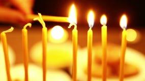 Eine Frau hält eine Kerze in ihrer Hand, mithilfe deren sie Kerzen von Chanukka beleuchtet Nahaufnahme verschieben Sie die Kamera