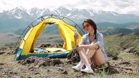 Eine Frau an ihrem Telefon während in ihrem Zelt und in Schlafsack stock video footage