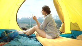 Eine Frau an ihrem Telefon während in ihrem Zelt und in Schlafsack stock video