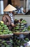 Eine Frau im beschäftigten Markt in Vietnam Stockfotografie