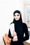 Eine Frau im hijab, das Dokumente verwahrt stockbild