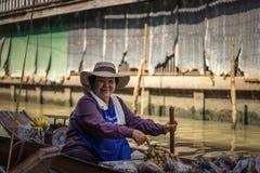 Eine Frau ist ein Verkäufer auf einem sich hin- und herbewegenden Markt Damnoen Saduak stockfoto