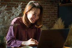 Eine Frau kauft im Internet beim Setzen des wenigen L?chelns auf ihr Gesicht stockbild