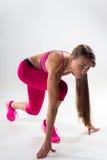 Eine Frau kleidete in der Sportkleidung an, die vorbereitet wurde, um zu laufen studio Weißes BAC Stockbild