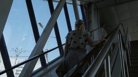 Eine Frau klettert oben die Rolltreppe in einem Geschäftszentrum oder einem Flughafen stock footage