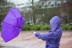 Eine Frau kämpft gegen den Sturm mit ihrem Regenschirm Lizenzfreies Stockbild