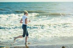 Eine Frau läuft entlang den Strand früh morgens in den Strahlen des aufgehende Sonne Lizenzfreies Stockbild