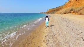 Eine Frau läuft entlang die Küstenlinie und die Kamera folgt ihr stock video