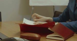 Eine Frau läuft Papiere auf dem Schreibtisch im Büro durch stock video footage