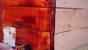 Eine Frau lackiert h?lzerne Planken Mit Holz, auf der Stra?e arbeiten stock footage