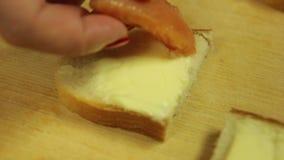 Eine Frau legt die Lachs-/Forellenscheiben auf einen Canape mit Butte stock video