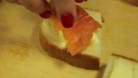 Eine Frau legt Lachsforellenscheiben auf einen Canape mit Butter stock video