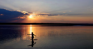 Eine Frau leitet das Wasser auf dem Hintergrund des Sonnenuntergangs ein Stockbilder