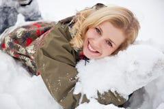 Eine Frau liegt am Schnee im Park Stockbilder