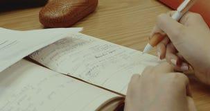 Eine Frau macht einen Eintritt im Tagebuch stock video footage
