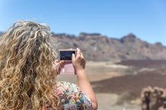 Eine Frau macht Fotos mit ihrem Handy in einer Wüstenlandschaft auf der Insel von Teneriffa an einem sehr sonnigen Tag stockbilder