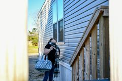 Eine Frau macht Gesichter in ein Hausfenster stockbilder