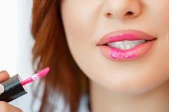 Eine Frau malt ihre Lippen mit einer B?rste Gro?e Details stockfotos