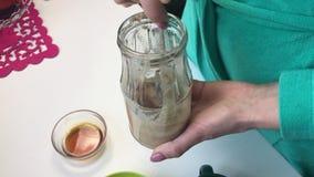 Eine Frau mischt Mehl mit flüssigem Honig in einem Glasgefäß Überprüft die Qualität der Mischung Für die Vorbereitung der Hefe fü stock video footage