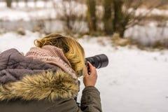 Eine Frau mit dem blonden Haar steht in einer Winterlandschaft Lizenzfreies Stockbild