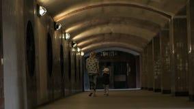 Eine Frau mit dem Händchenhalten eines kleinen Mädchens laufen den Tunnel durch stock video footage