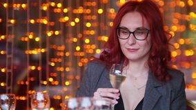 Eine Frau mit dem roten Haar, das durch Tabelle im Restaurant und in trinkendem Champagner sitzt stock footage