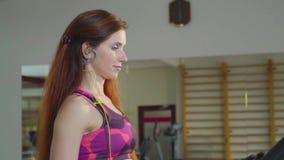 Eine Frau mit dem roten langen Haar geht auf eine Tretmühle und hört Musik auf Kopfhörern, Zeitlupe stock footage
