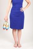Eine Frau mit einem blauen Kleid, das hohe Absätze hält Stockfotos