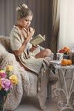 Eine Frau mit einem Buch und ein reifer Apfel in einer Hand Stockbild