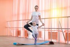 Eine Frau mit einem Kind, das Yoga tuend steht Lizenzfreie Stockfotos