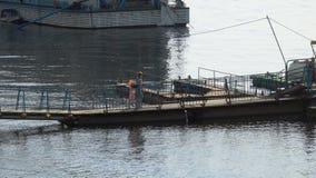 Eine Frau mit einem Kind geht entlang die Brücke zum Pier stock footage