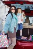 Eine Frau mit einem Kind nach Einkaufslast das Auto Lizenzfreie Stockfotos