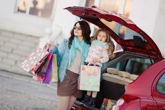 Eine Frau mit einem Kind nach Einkaufslast das Auto Lizenzfreie Stockfotografie