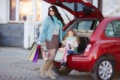 Eine Frau mit einem Kind nach Einkaufslast das Auto Lizenzfreie Stockbilder