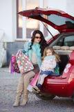 Eine Frau mit einem Kind nach Einkaufslast das Auto Stockbild
