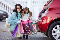 Eine Frau mit einem Kind nach Einkaufslast das Auto Stockfotos