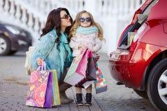 Eine Frau mit einem Kind nach Einkaufslast das Auto Stockfoto
