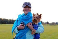 Eine Frau mit einem kleinen Hund in ihren Händen Stockbild