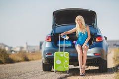 Eine Frau mit einem Koffer nahe dem Auto Stockbild