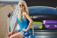 Eine Frau mit einem Koffer nahe dem Auto Stockbilder