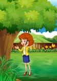 Eine Frau mit einem Mobiltelefon, das unter dem Baum steht Lizenzfreies Stockbild