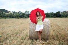 Eine Frau mit einem roten Regenschirm Stockbilder